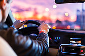 Driving a car at night -man driving his modern car at night in a city (shallow DOF; color toned image)
