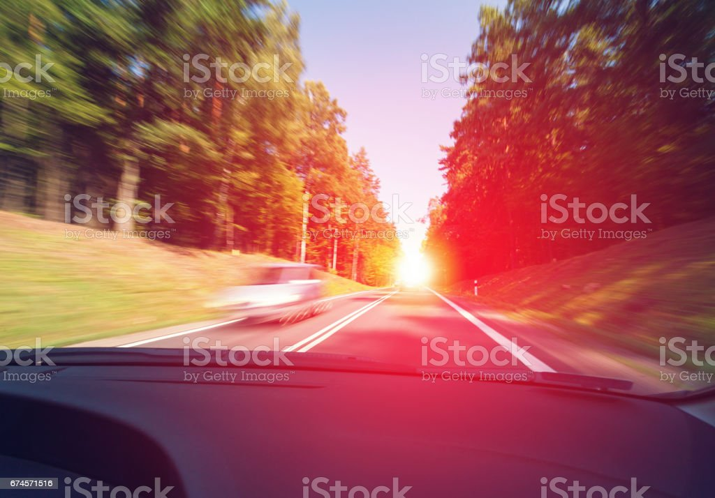 Driving a car in the morning to the sunrise in good weather conditions stock photo