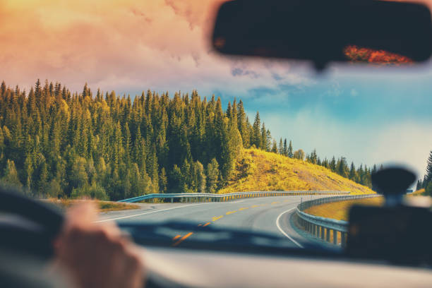 Driving a car on a mountain road. View from the windscreen of beautiful nature of Norway Driving a car on a mountain road. View from the windscreen of beautiful nature of Norway road trip stock pictures, royalty-free photos & images