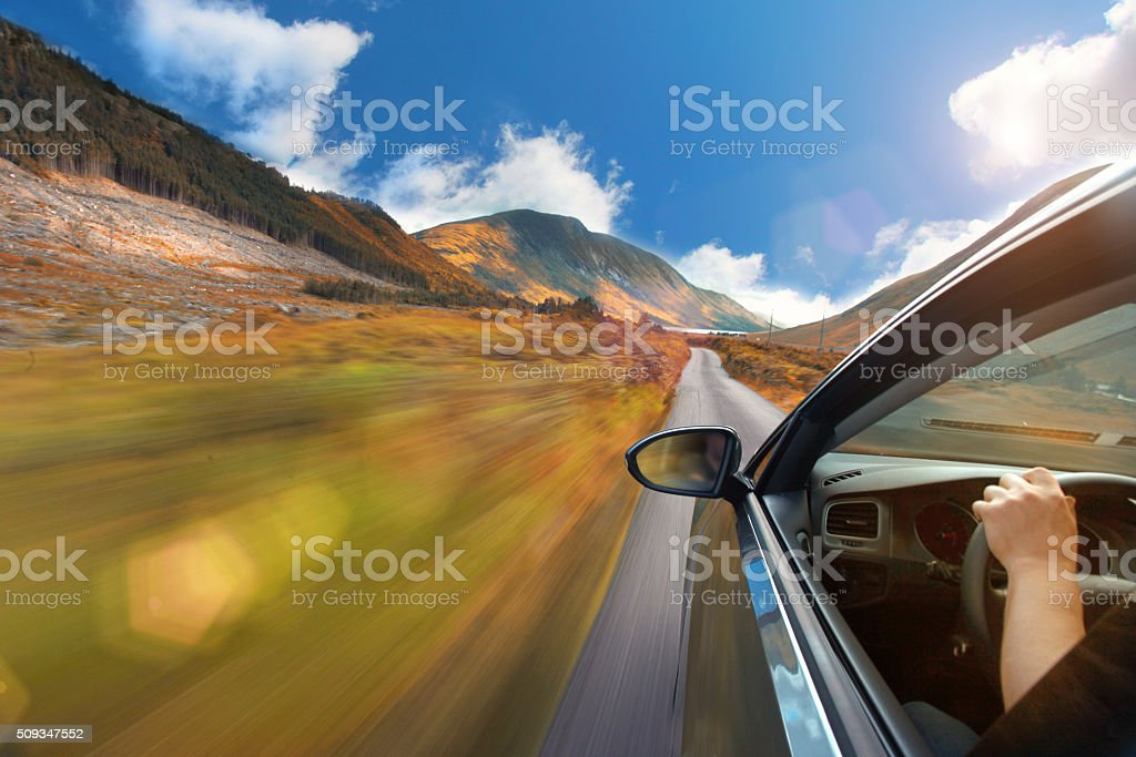 Driving a car on a mountain road with idyllic landscape stock photo