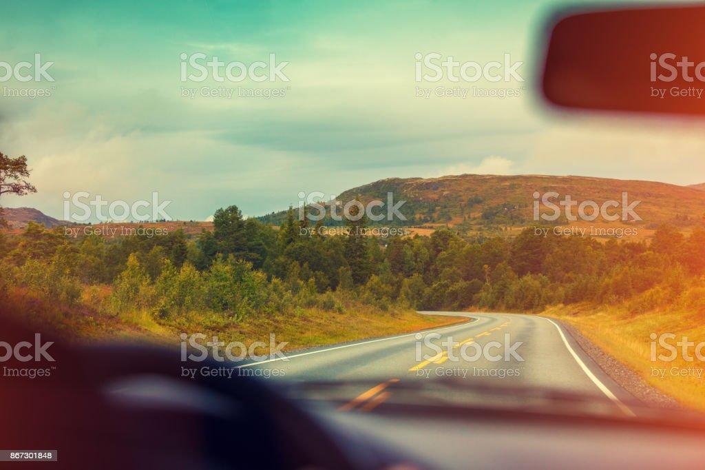 Autofahren bei Sonnenuntergang an der Bergstrasse. Blick von der Windschutzscheibe. Natur von Norwegen – Foto