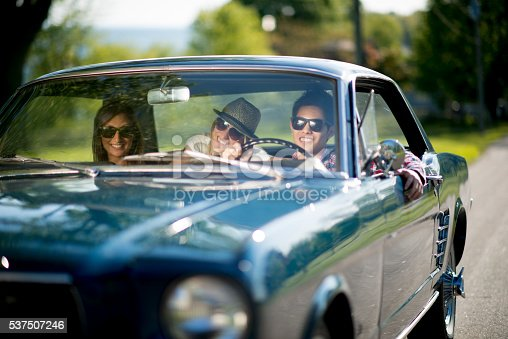 A multi-ethnic group of college age students are taking a road trip together on their spring break. They are driving a classic car on a sunny day.