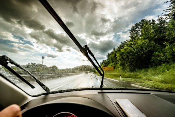 driving a rainy highway Driving through a rainy highway windshield wiper stock pictures, royalty-free photos & images