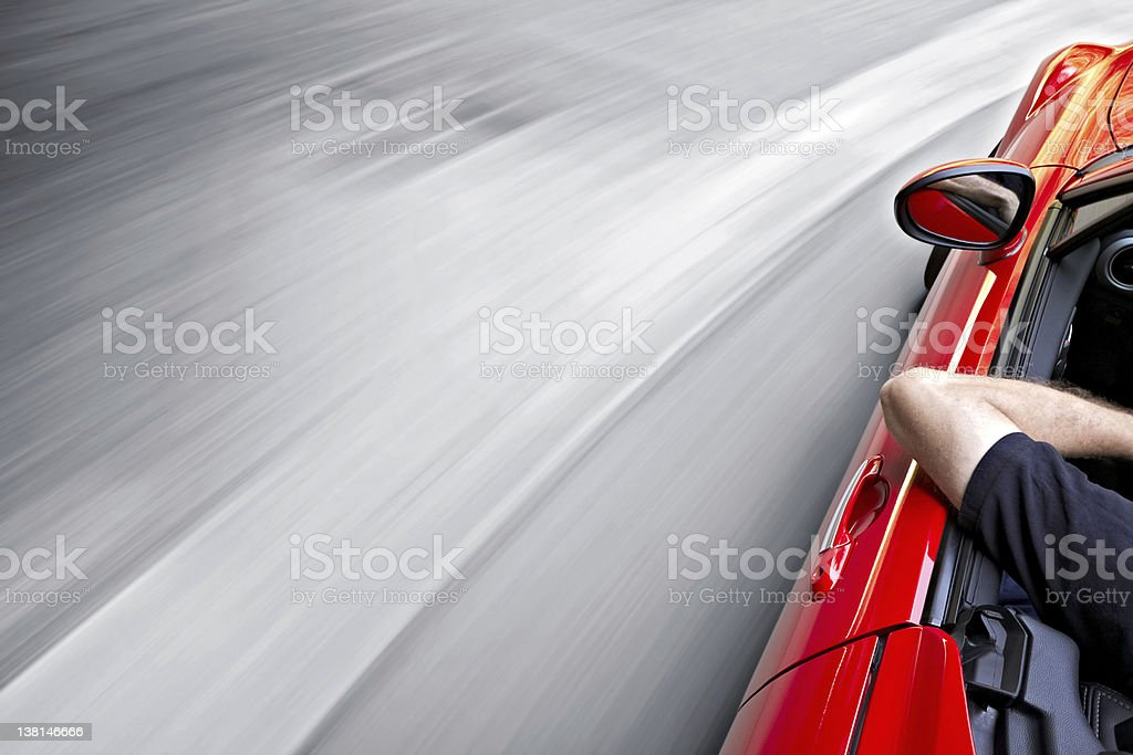 Driving a red car around a curve royalty-free stock photo