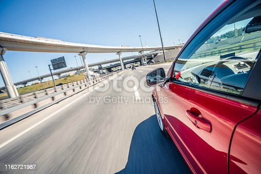Driving a red car in the on the highway