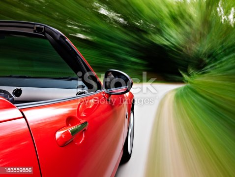 Motion blur shot while driving a red sports cabriolet