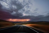 Driving on a desert road with thunderstorm ahead