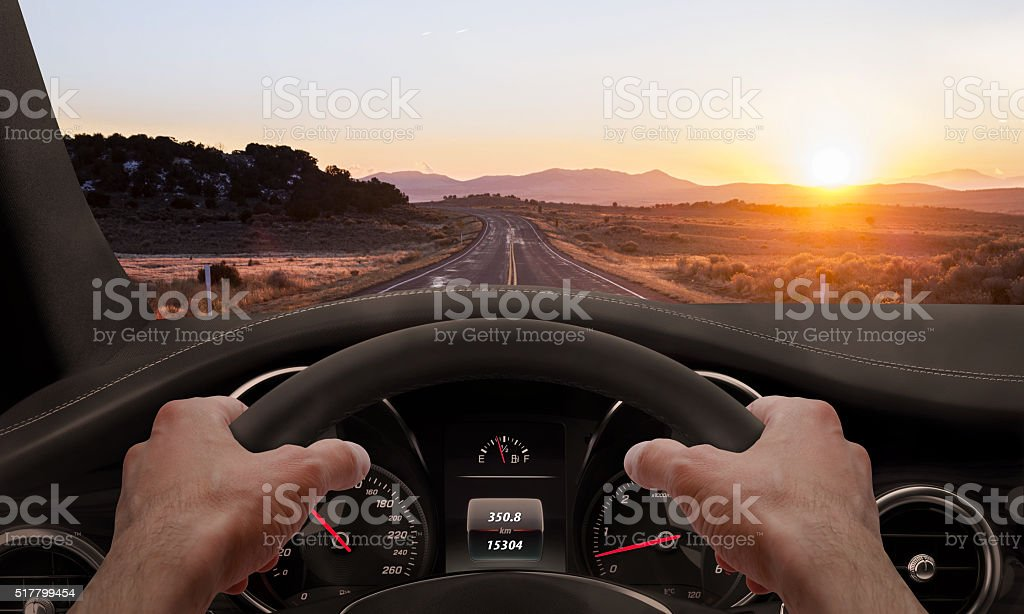 Driving at sunset. View from the driver angle while - Royalty-free Asphalt Stock Photo