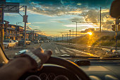 driving at the sunset,View from the driver angle car,to the golden sun
