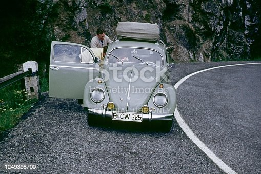 Alps, northern Italy, 1961. Driving break on the edge of a serpentine road. Holidaymakers from Central Europe take a break on the way to an Italian vacation spot.