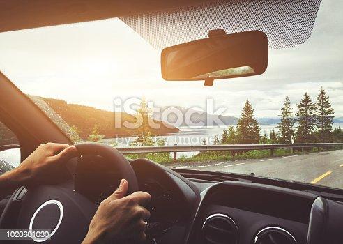 driving car in Norway, roadtrip, hands of driver on steering wheel