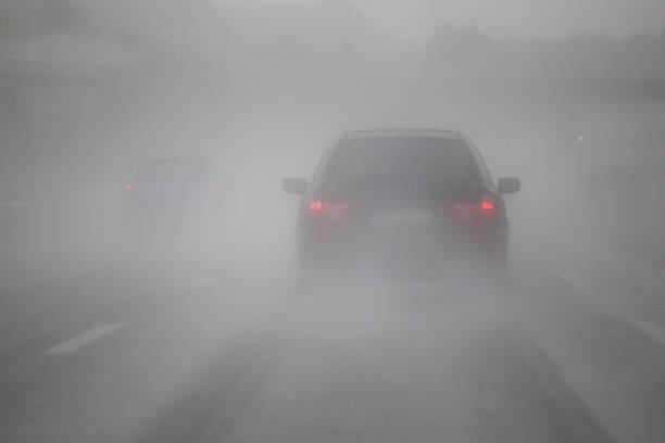 guida auto in nebbia - nebbia foto e immagini stock