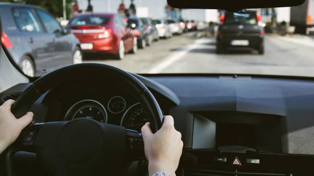 volant de voiture sur la route. mains sur le volant à l'intérieur d'une voiture - embouteillage photos et images de collection