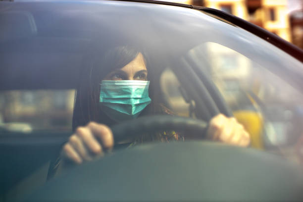 driving car with face mask stock photo