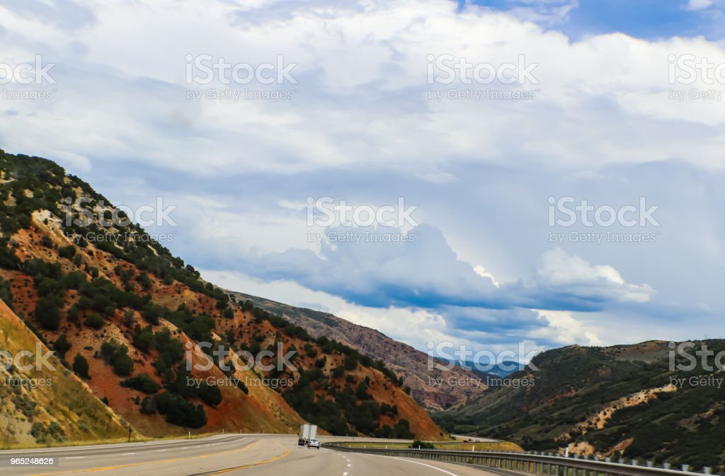 Driving curved road through the mountians with beautiful blue cloudy sky and tunnel in the distance royalty-free stock photo