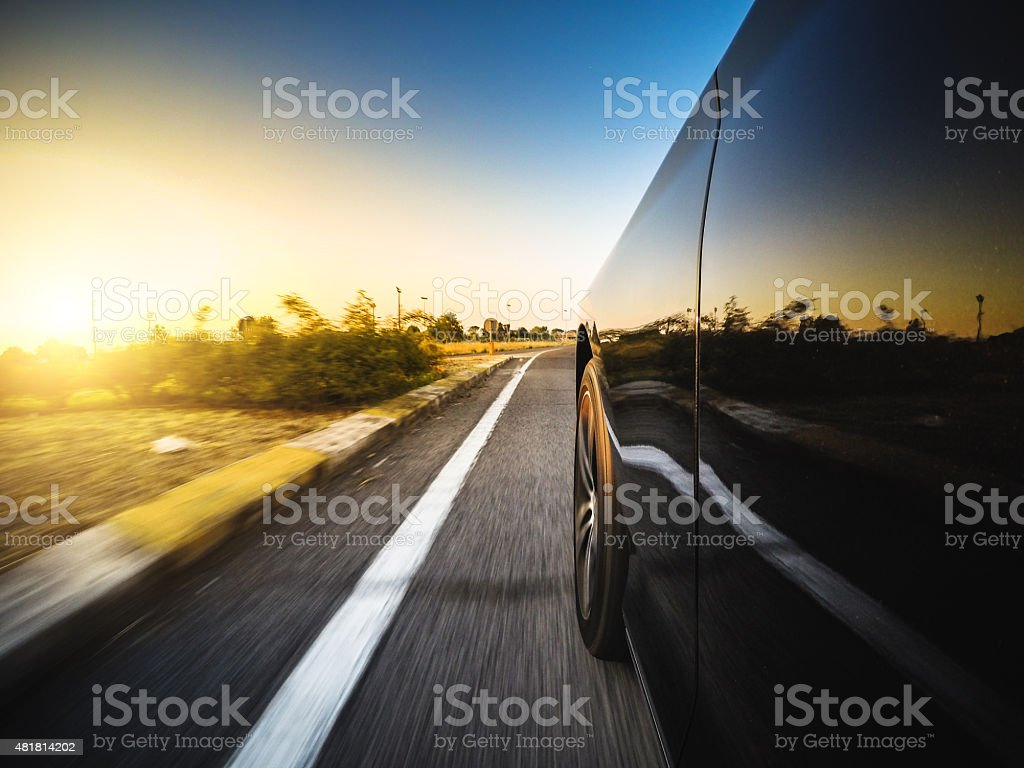 Driving fast at sunset stock photo