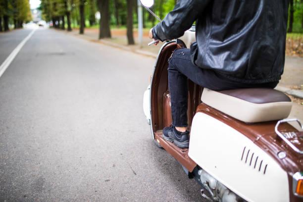 conduire vite. portrait de jeune homme au volant scooter rue de près. - moped photos et images de collection