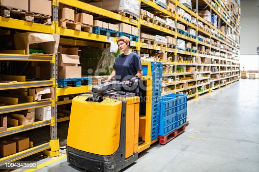 istock Driving forklift loaded with crates in warehouse 1094343590