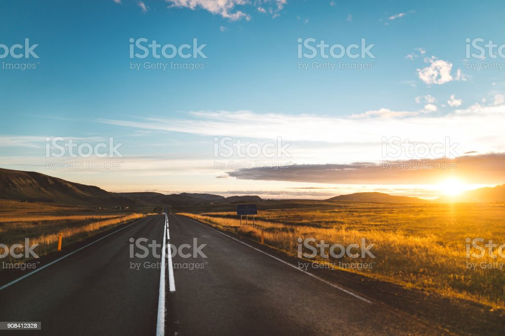 Driving Iceland's ring road self-drive tour.Number 1 road on Iceland, scenic panoramas near the highway.Tourist attraction and campers tour route.Beautiful golden sunset illuminates asphalt road. stock photo