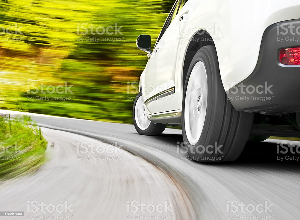 Driving in a curve Low angle shot from the back of a car driving fast in a curve See more car driving images in my portfolio Alloy Wheel Stock Photo