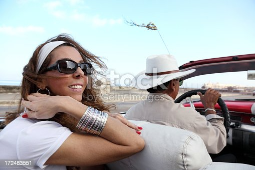 Smiling young woman rides in an old convertible along the Malecon Avenue in Havana, Cuba.