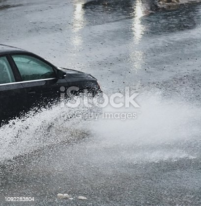 A compact sedan navigates a flooded portion of highway after heavy rains.