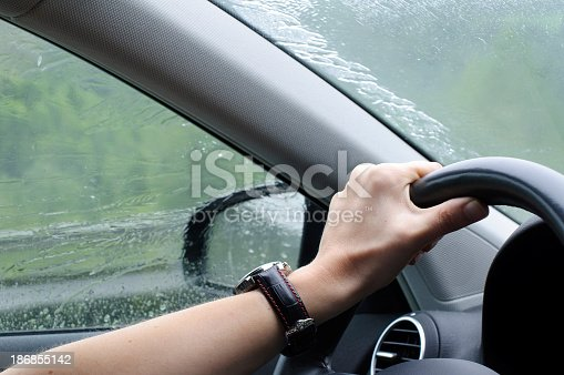 1054750504 istock photo Driving in rainy weather with car 186855142