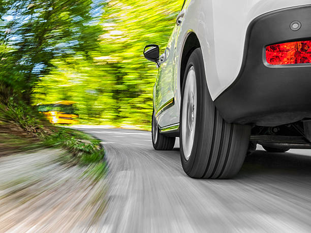 Driving in the curve Low angle shot of a car driving on the road bumper stock pictures, royalty-free photos & images