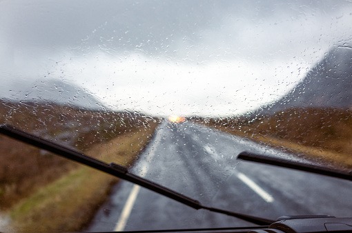 Window wipers clearing rain on a journey through Glencoe in Scotland.