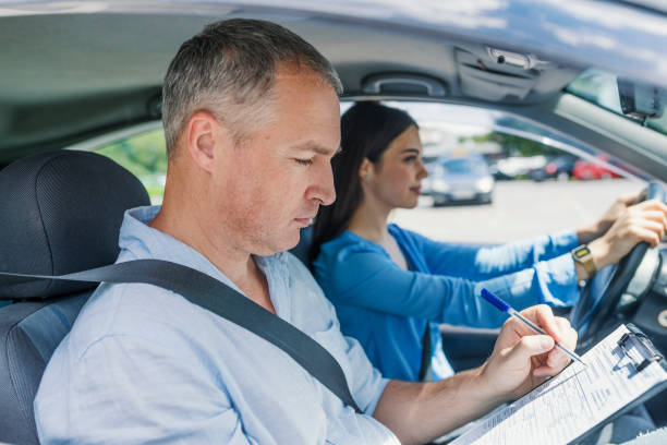 Driving instructor and woman student in examination car Driving instructor and woman student in examination car. Driving instructor inside a car with student driver doing checklist. Young woman on a driving test with her instructor driving instructor stock pictures, royalty-free photos & images