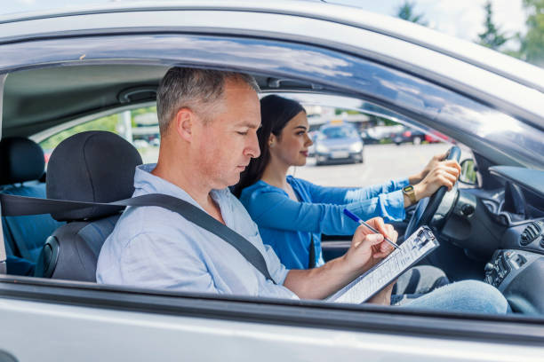 Driving instructor inside a car with student driver doing checklist Driving instructor and woman student in examination car. Driving instructor inside a car with student driver doing checklist. Young woman on a driving test with her instructor driving instructor stock pictures, royalty-free photos & images