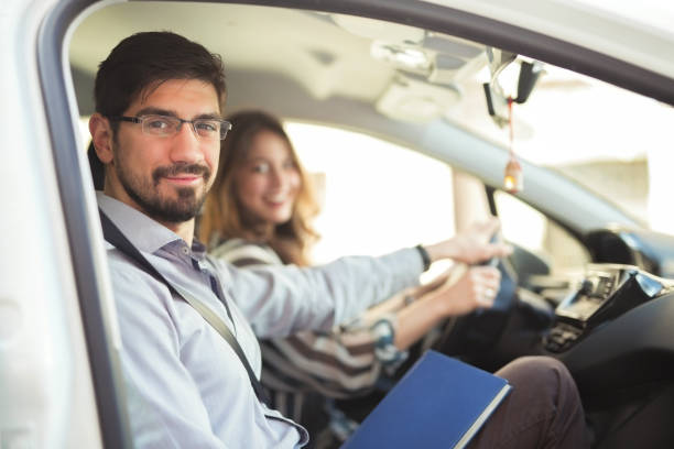 Driving Instructor Driving instructor is teaching his student how to drive a car driving instructor stock pictures, royalty-free photos & images