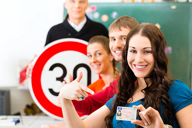 Driving instructor with his class Driving school - driving instructor in his class and a female student driver looking in the Camera, in the background are traffic signs driving instructor stock pictures, royalty-free photos & images