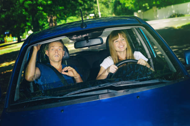 Driving lesson: terrified man teaching  happy girlfriend to drive A beautiful young woman learning to drive a car looks delighted - her boyfriend and driving teacher looks terrified. driving instructor stock pictures, royalty-free photos & images