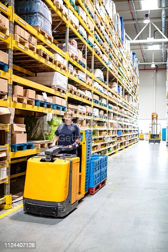 istock Driving loaded forklift in warehouse 1124407126