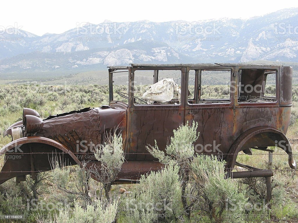 Rusty Model-T auto with dinosaur at the wheel.
