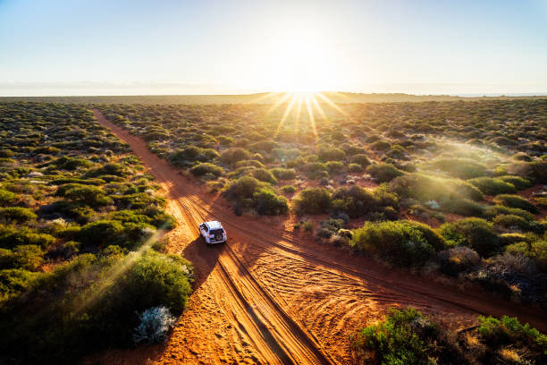 Driving off-road in Western Australia at sunset Driving off-road in Western Australia at sunset, aerial view. Francois Peron National Park outback stock pictures, royalty-free photos & images