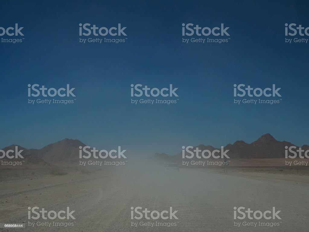 Driving offroad vehicle on road trip through misty unpaved road among desert and mountain landscape foto stock royalty-free