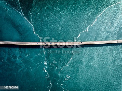 Aaerial photograph of the beautiful sea and bridge in Iceland. Cars are crossing the bridge to reach their destination.