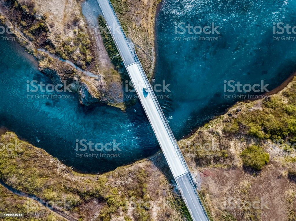 Driving on a bridge over deep blue water stock photo