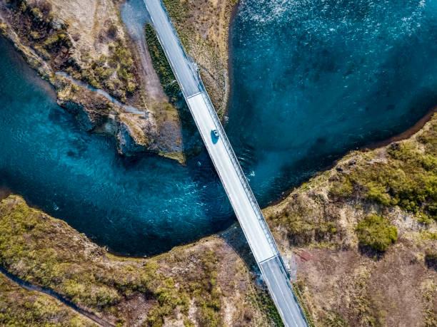bir köprüde derin mavi su üzerinde sürüş - bridge stok fotoğraflar ve resimler