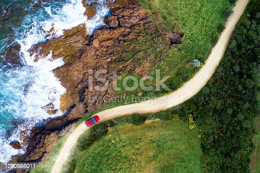 istock Driving on a seaside road approaching a beach, seen from above 1290666011