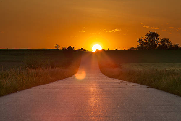 Driving on an asphalt road towards the setting sun Driving on an empty open asphalt road towards the setting sun. dark before dawn stock pictures, royalty-free photos & images