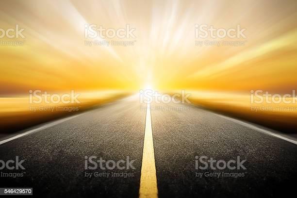 Photo of Driving on an blurred empty asphalt road twilight sky