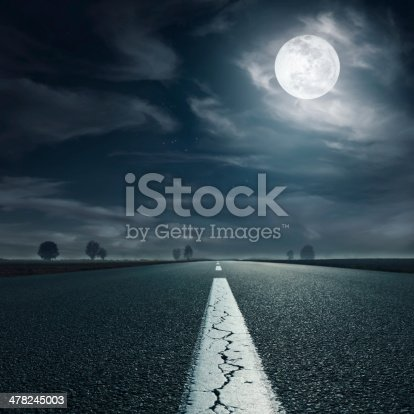 Driving on an empty asphalt road towards the full moon