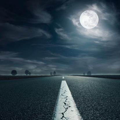 Driving on an empty asphalt road towards the full moon