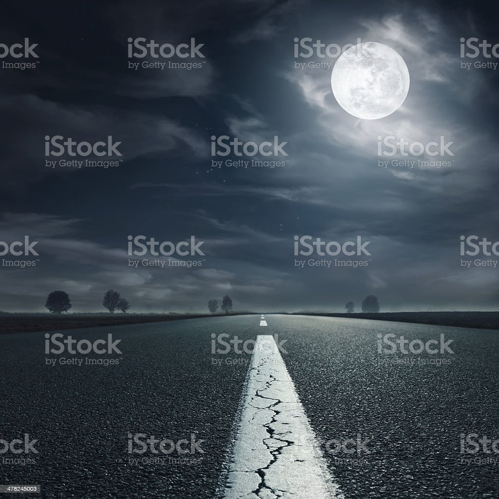 Driving on an empty highway towards the full moon stock photo
