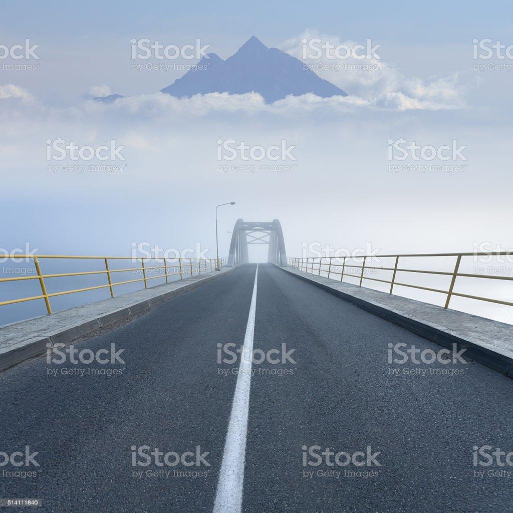 Driving on an empty mountain road across the bridge stock photo