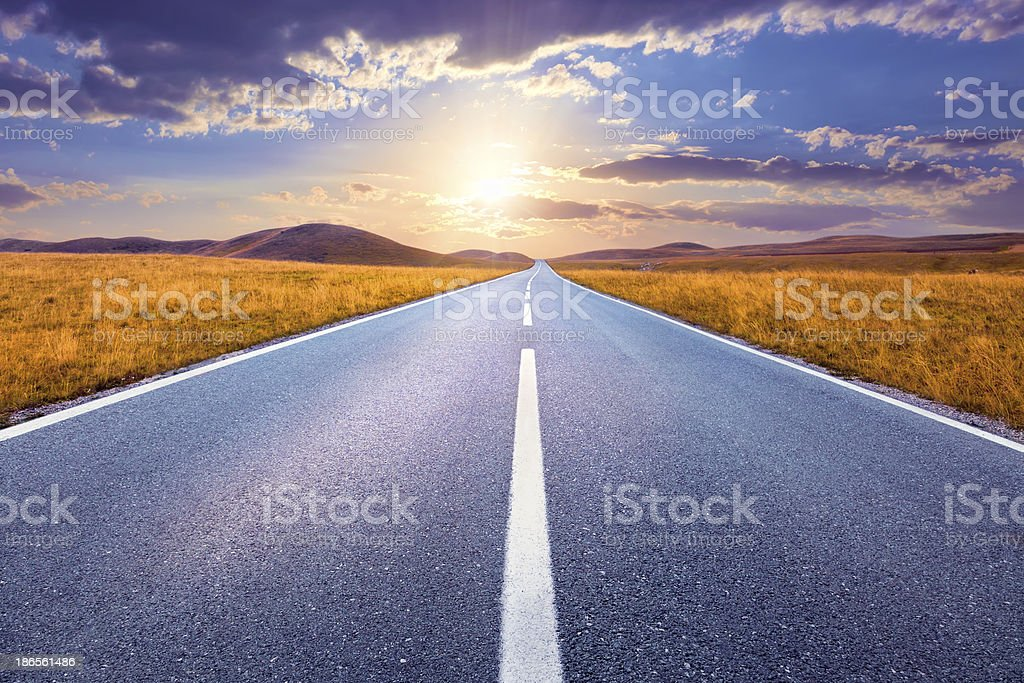 Driving on an empty road towards the setting sun stock photo