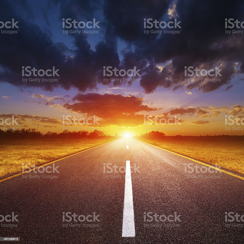 Driving on an empty road towards the setting sun royalty-free stock photo